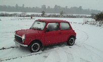 Mini in the snow with lights on